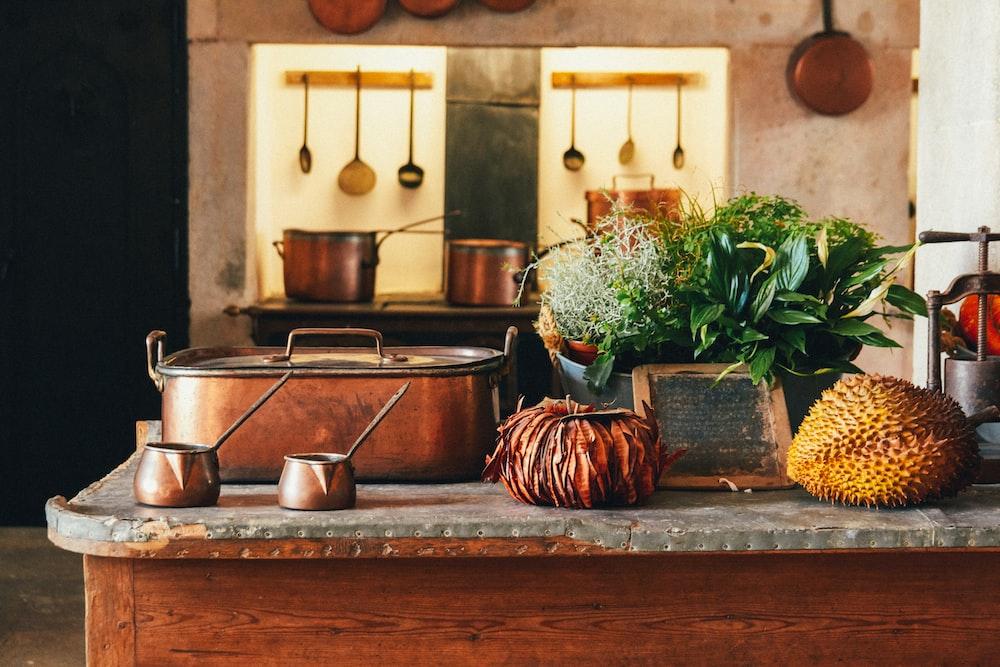 коричневая металлическая кастрюля возле фруктов и зеленых листьев растений на столе