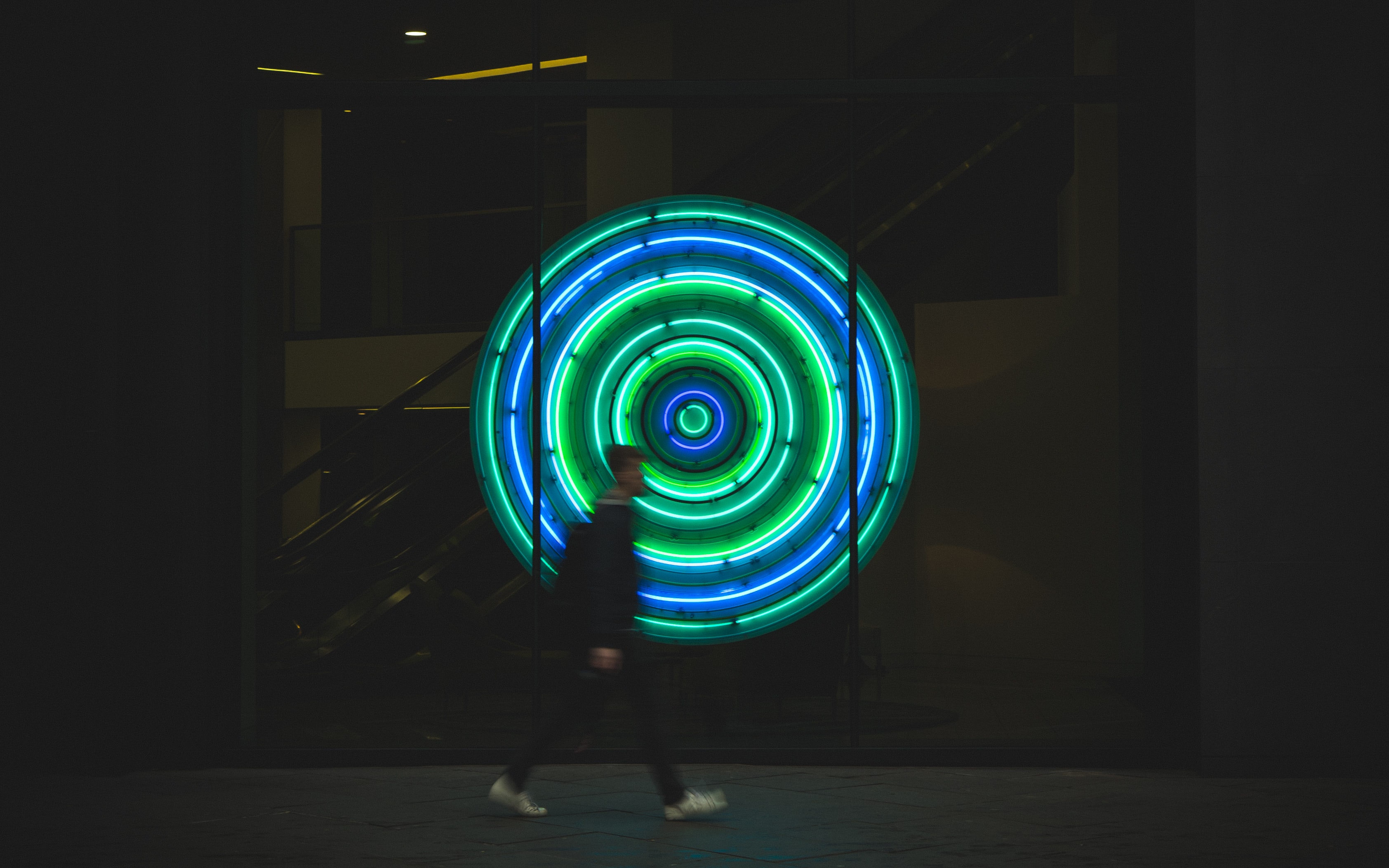 man walking near neon signage
