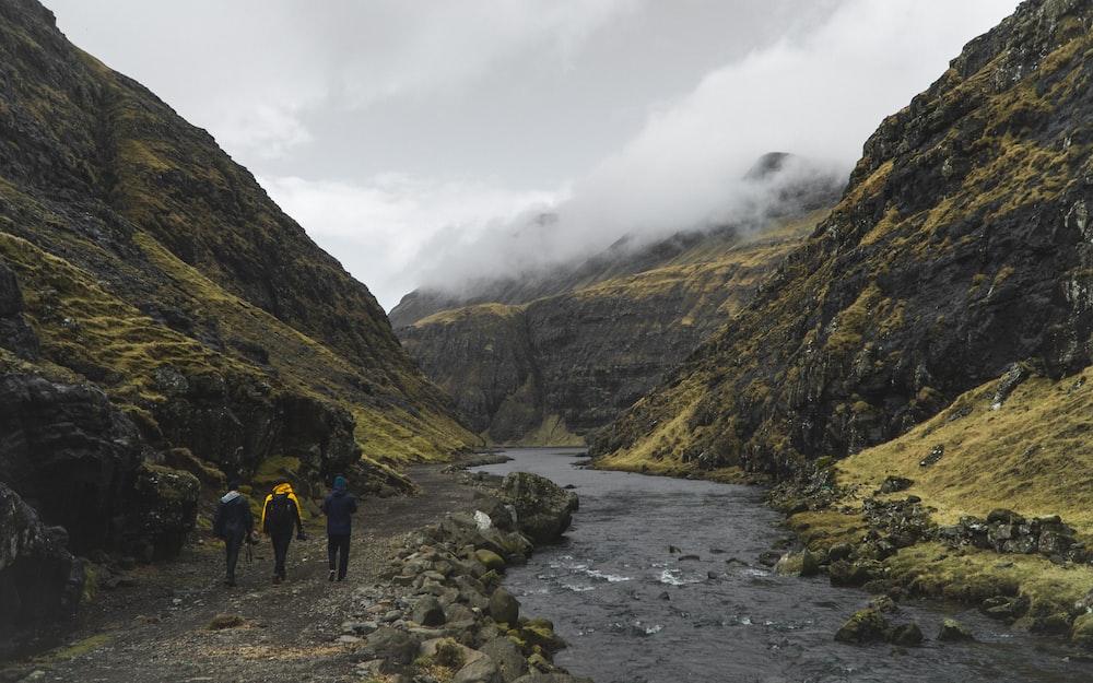 three person walking near river