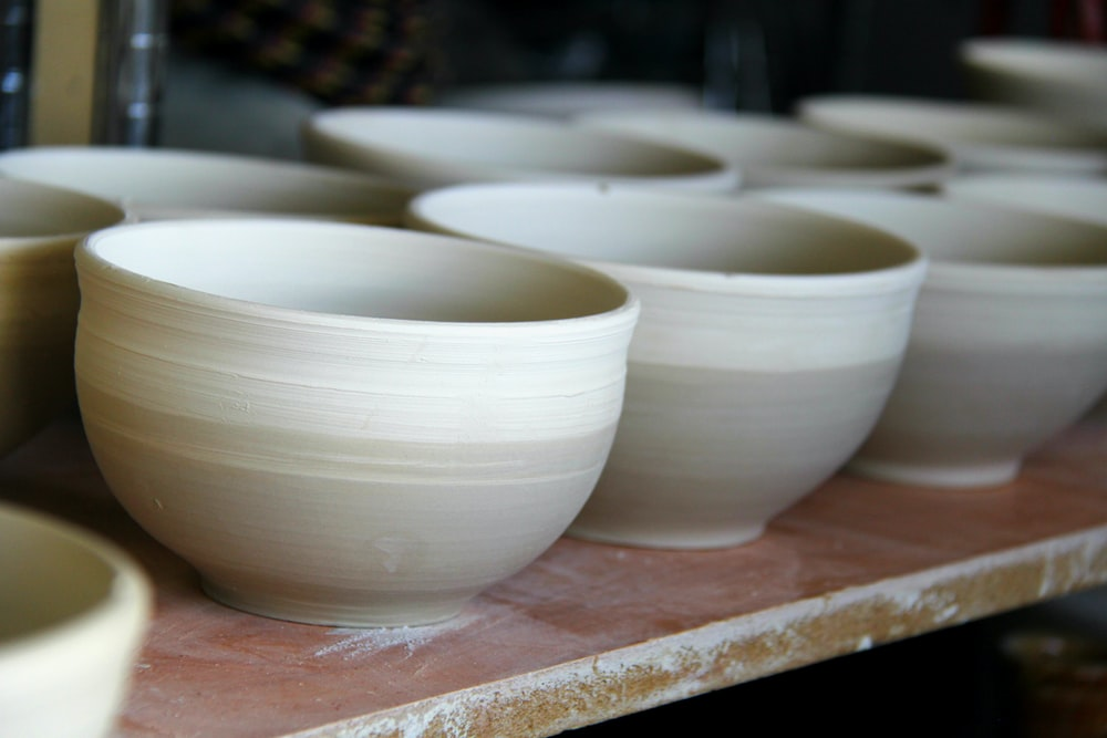 white-and-grey clay pots on brown wooden plank