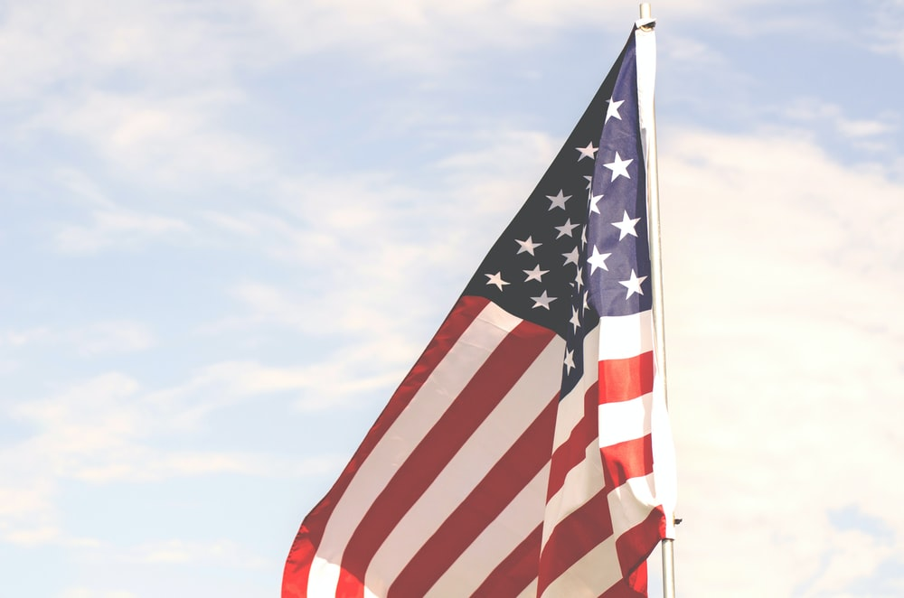U.S.A. flag under cloudy sky during daytime