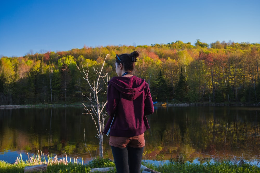 woman wearing red hoodie while standing near lake