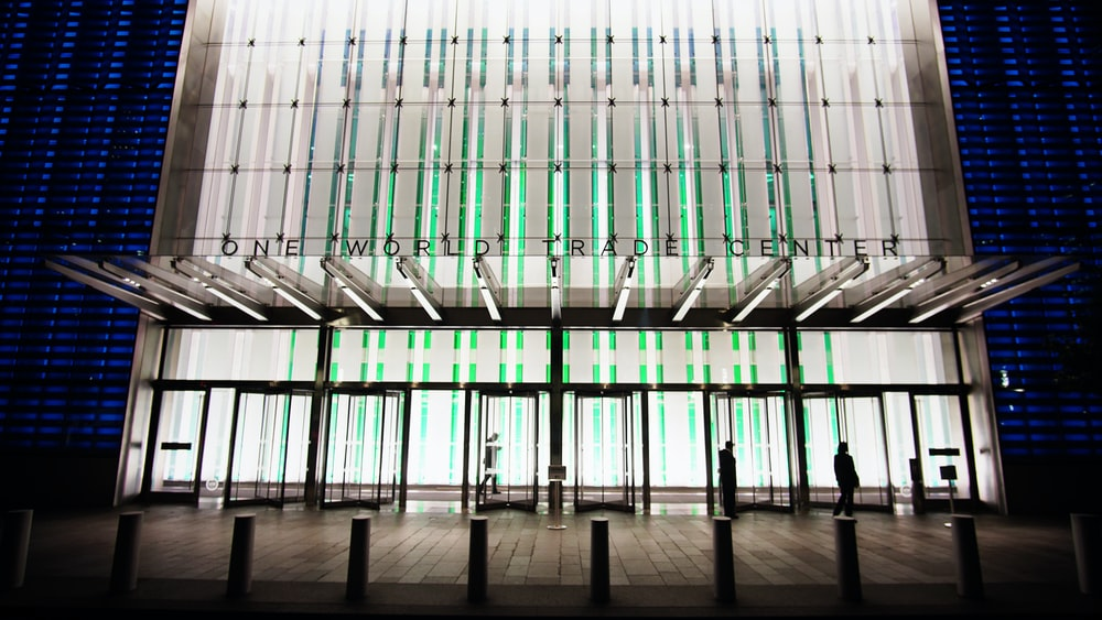 photo of white, blue, and green concrete building with glass