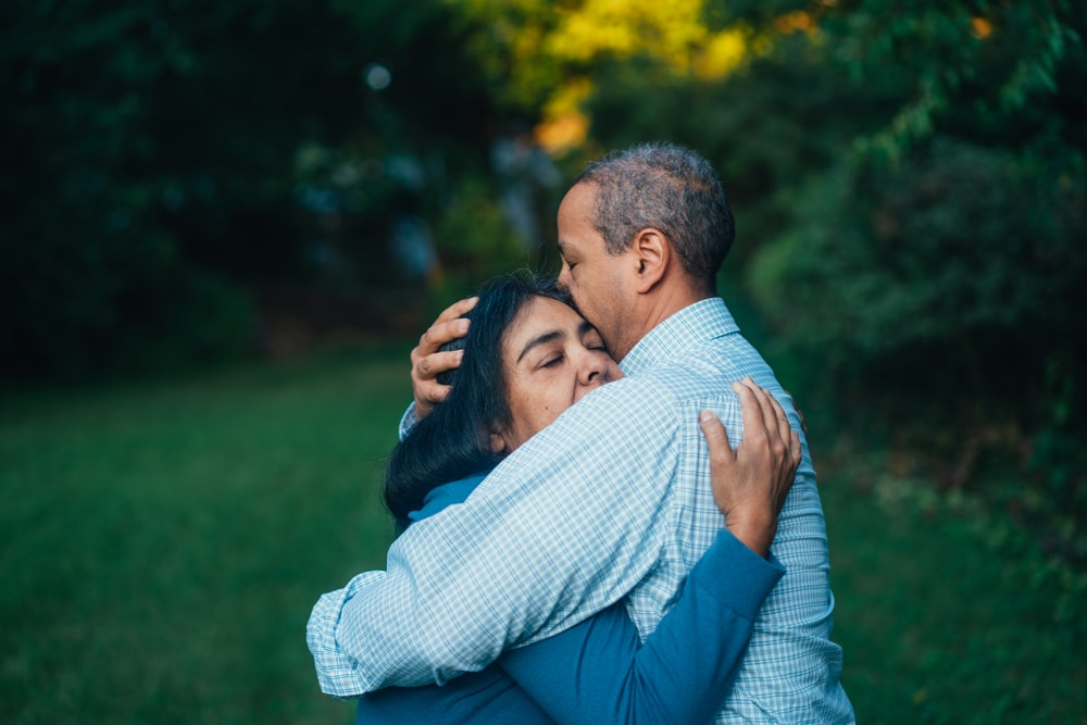man hugging woman near trees