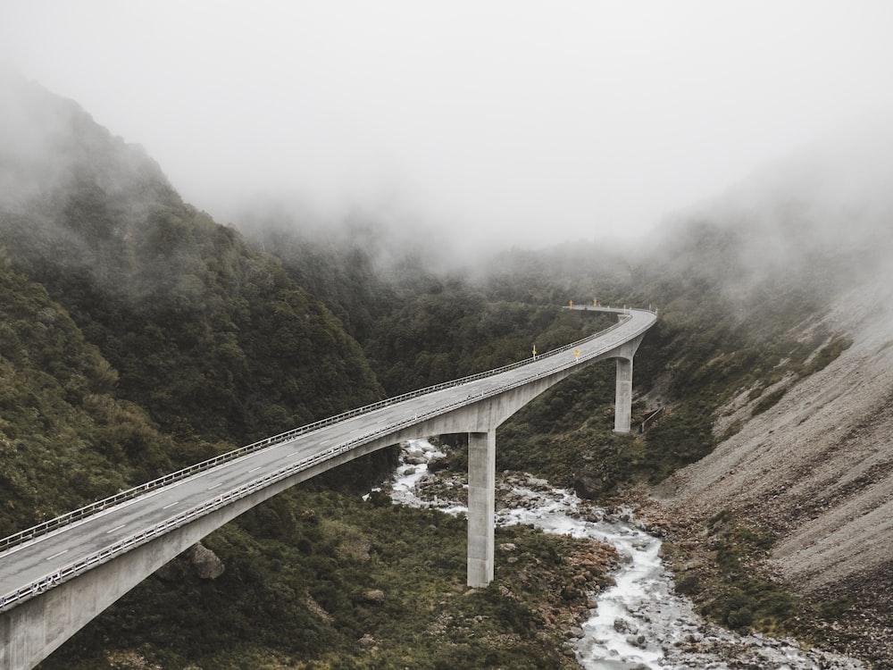 concrete bridge near mountains surrounded by fog