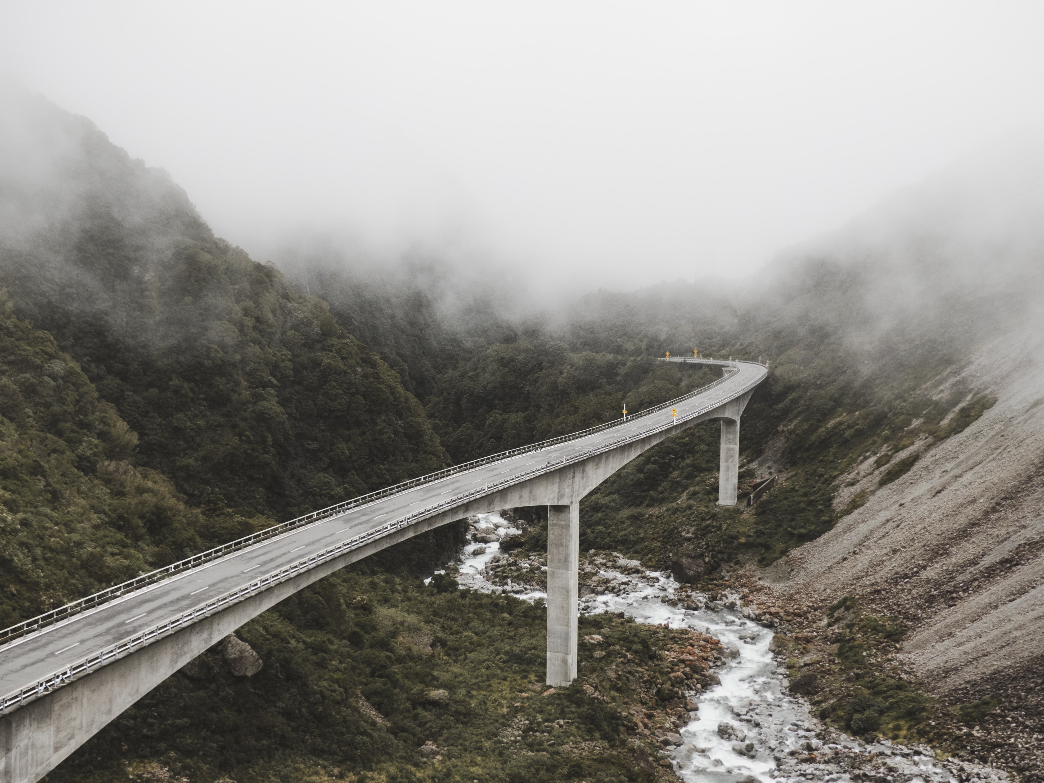 concrete bridge near mountains surrounded by fog