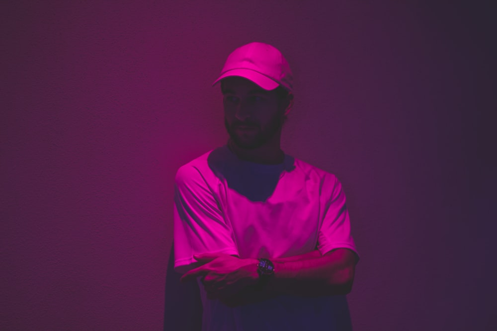 man leaning of wall with purple light in fashion photography