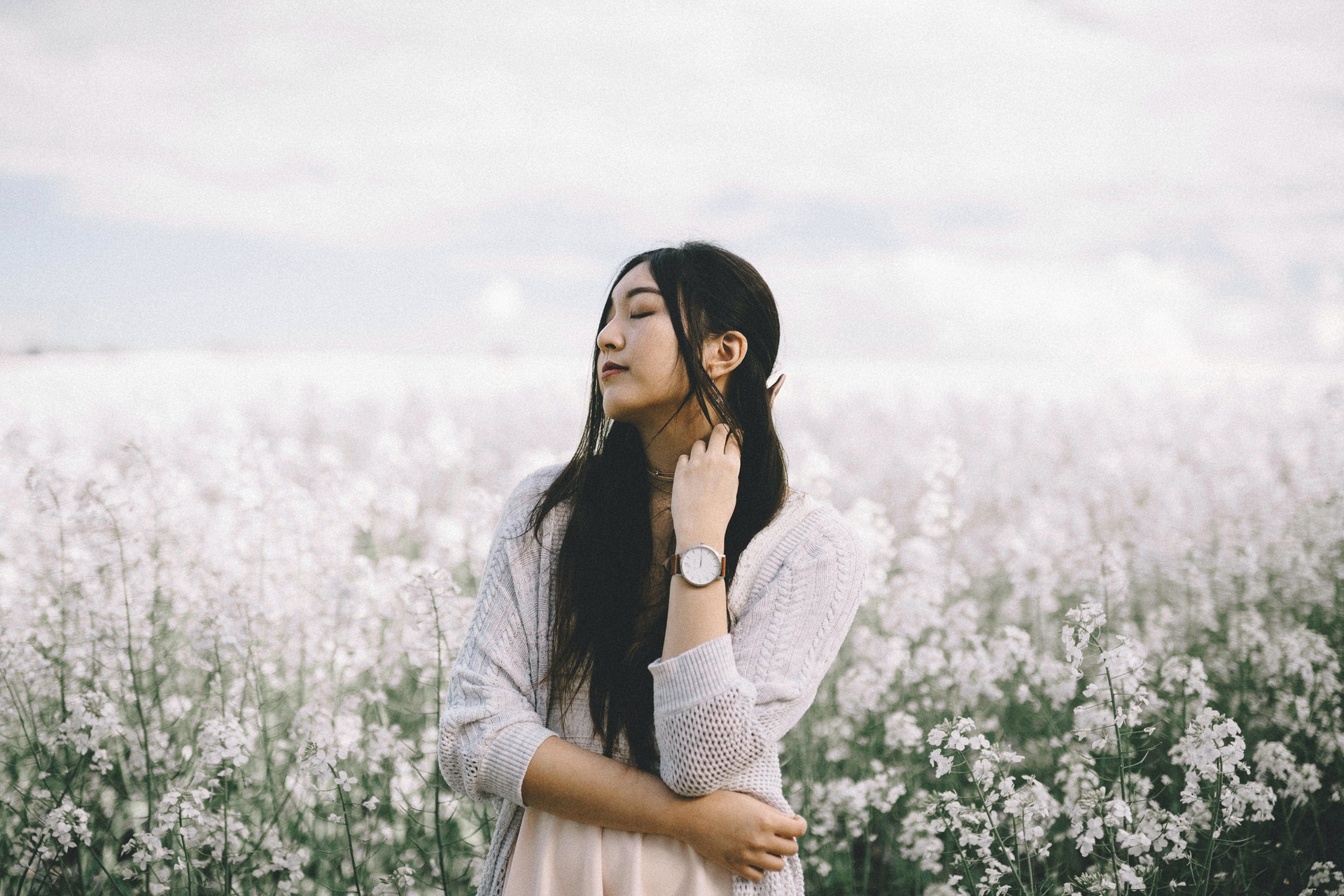 woman wearing peach inner top with gray knitted cardigan standing behind white flowerfield during daytime photography