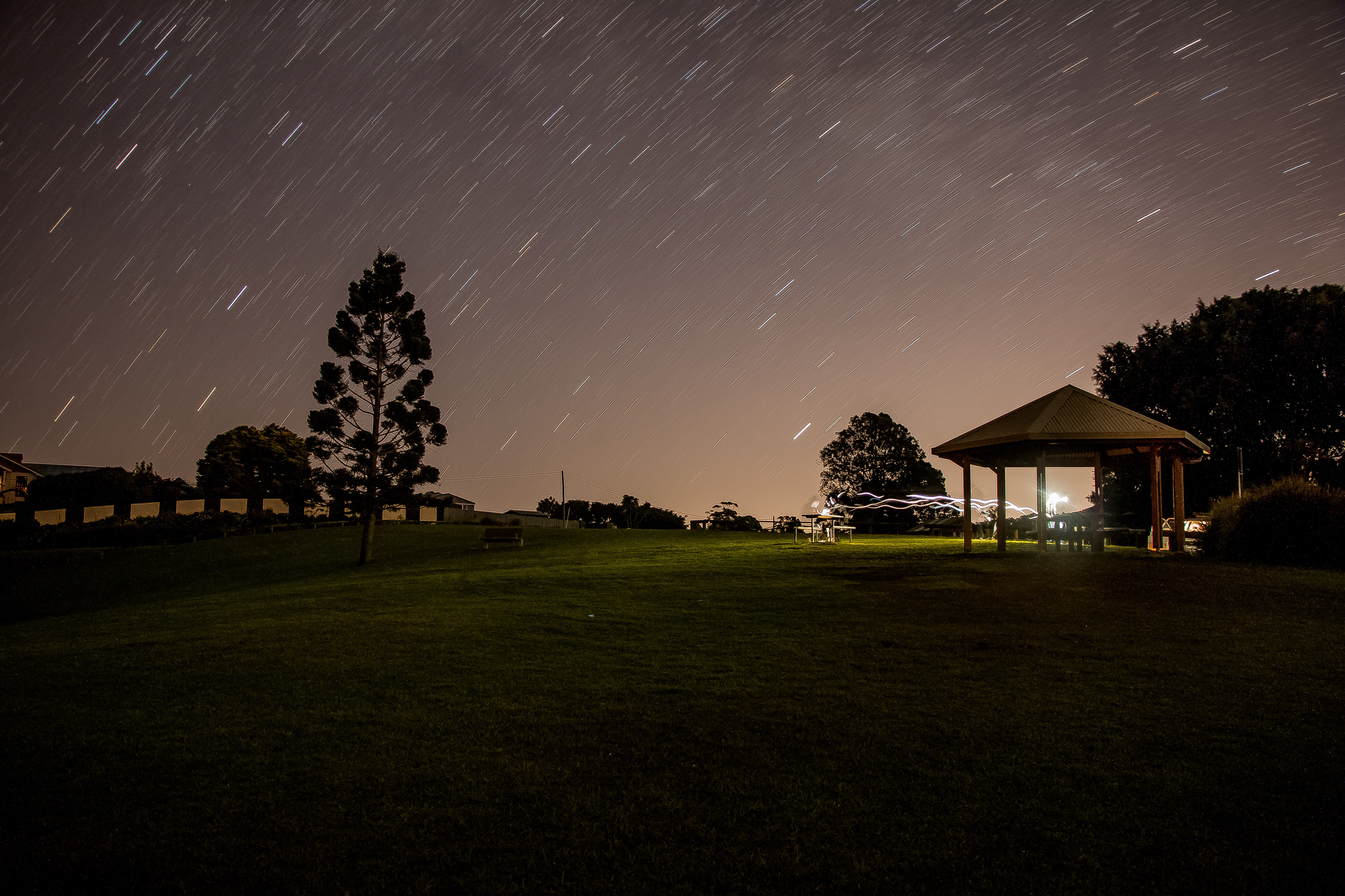 brown gazebo under starry night in time lapse photography