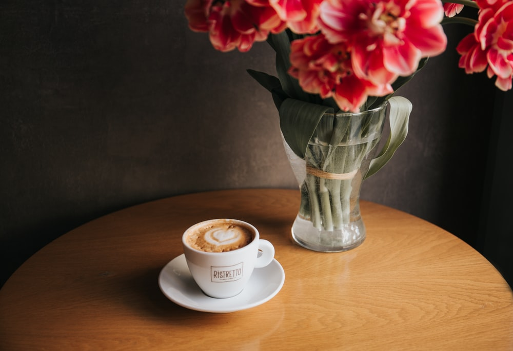 clear glass vase with red petaled flowers near cup filled with coffee both on round brown wooden table
