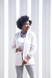 woman wearing white notched-lapel blazer and grey fitted jeans