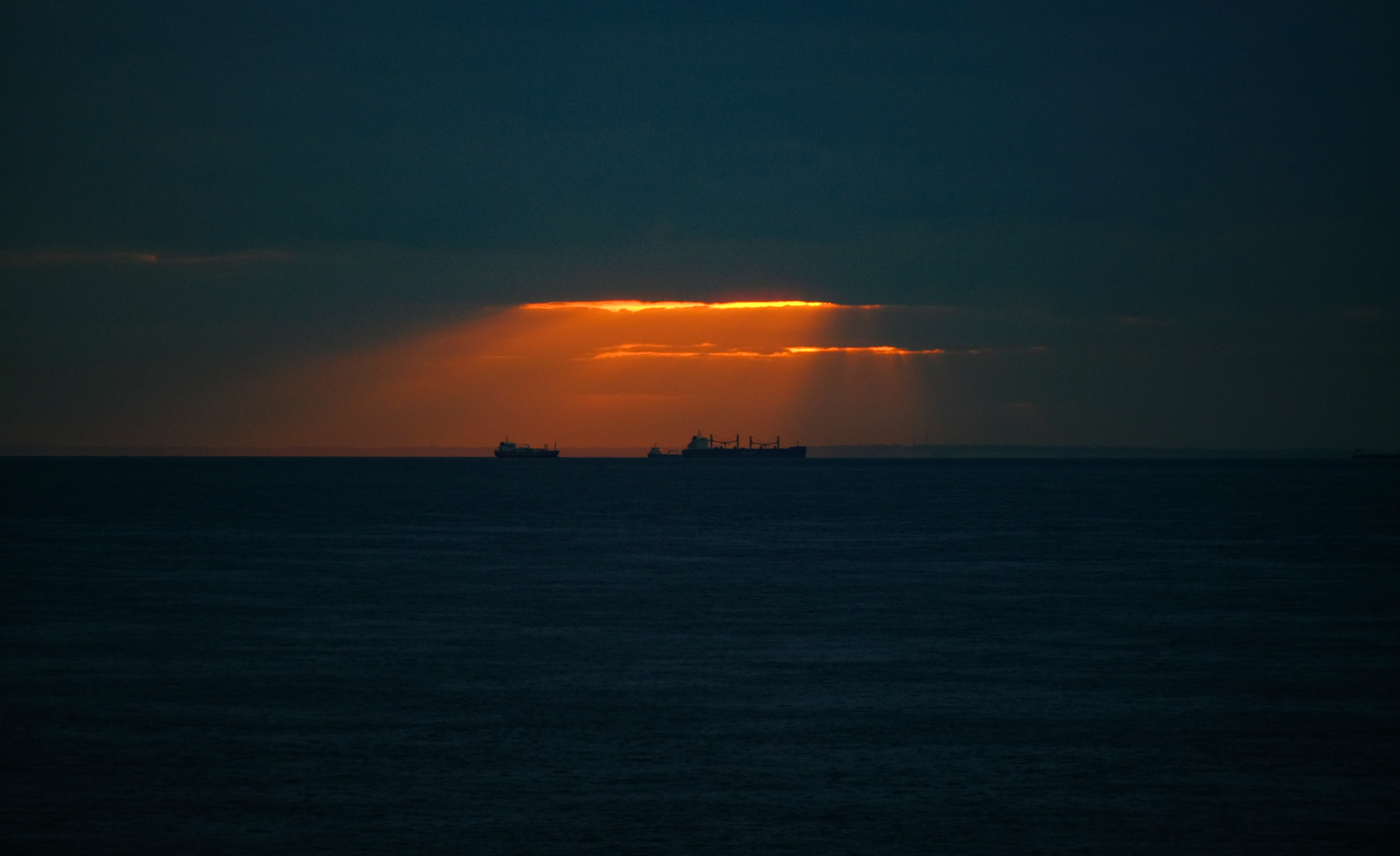 silhouette of two ships on body of water