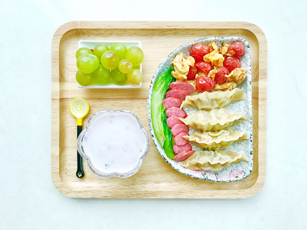 food on ceramic plates on square wooden tray