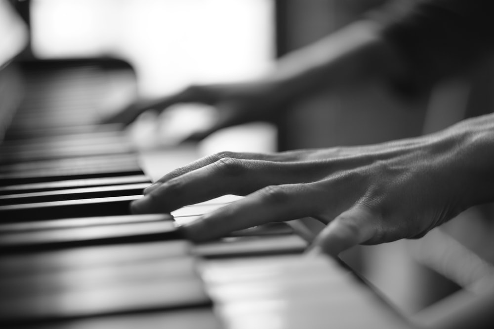greyscale photo of person playing piano