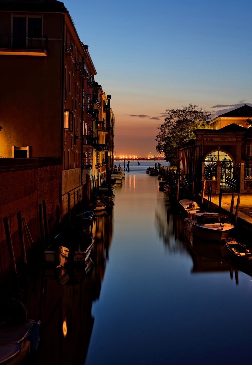landscape photo of river with boats beside a building