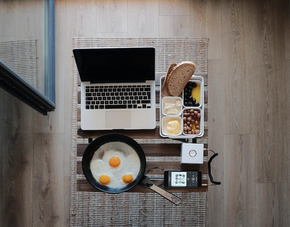 фотография MacBook Pro, сковорода с яйцами и хлебом на сером коврике