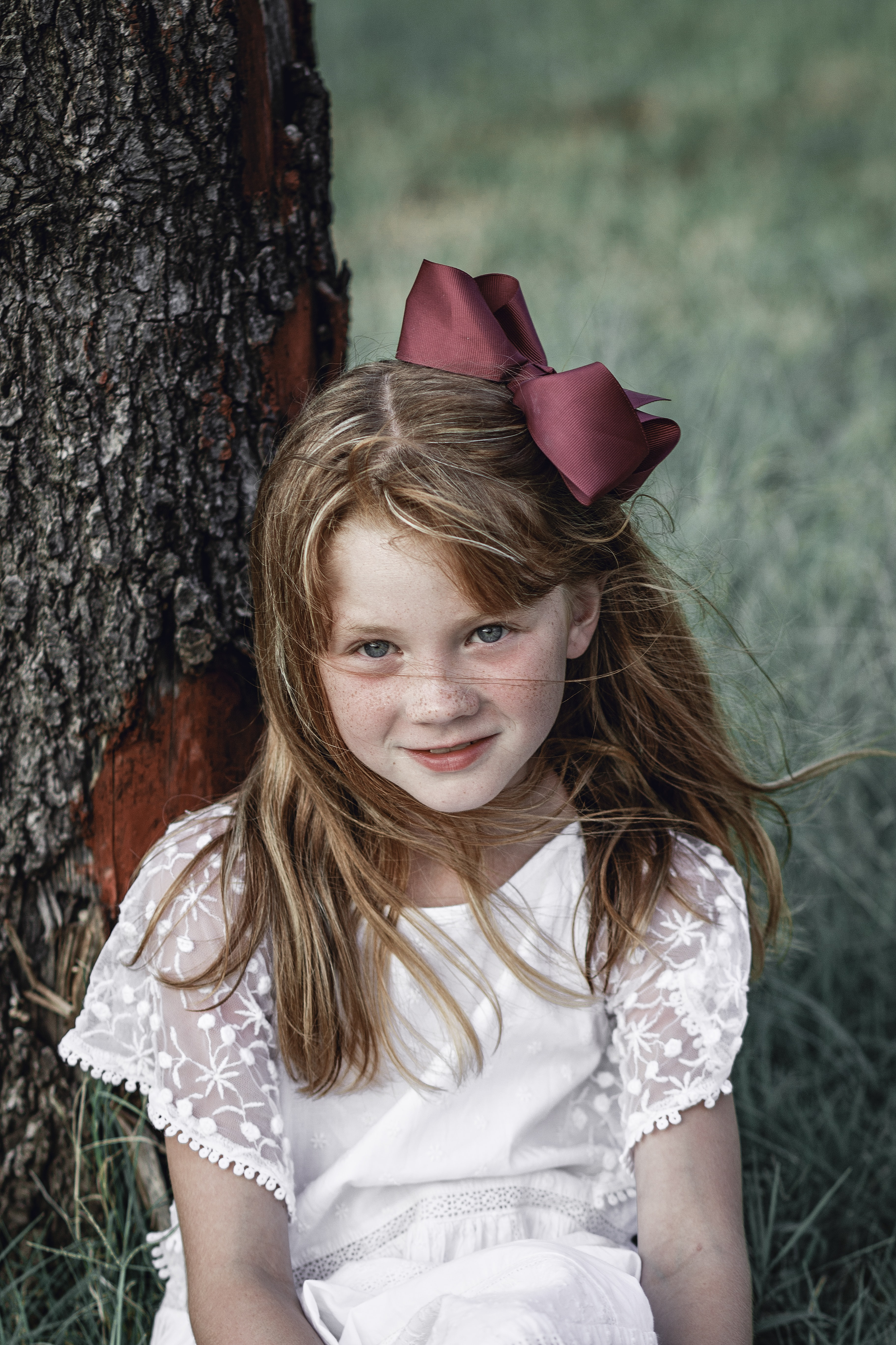 girl sitting beside tree while smiling
