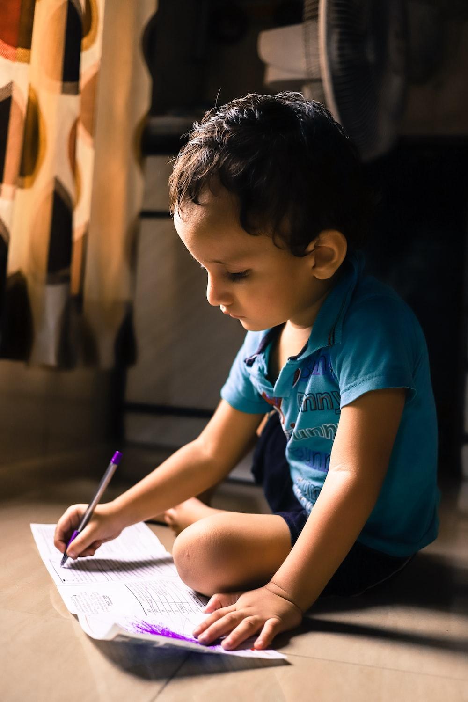 boy writing on white paper