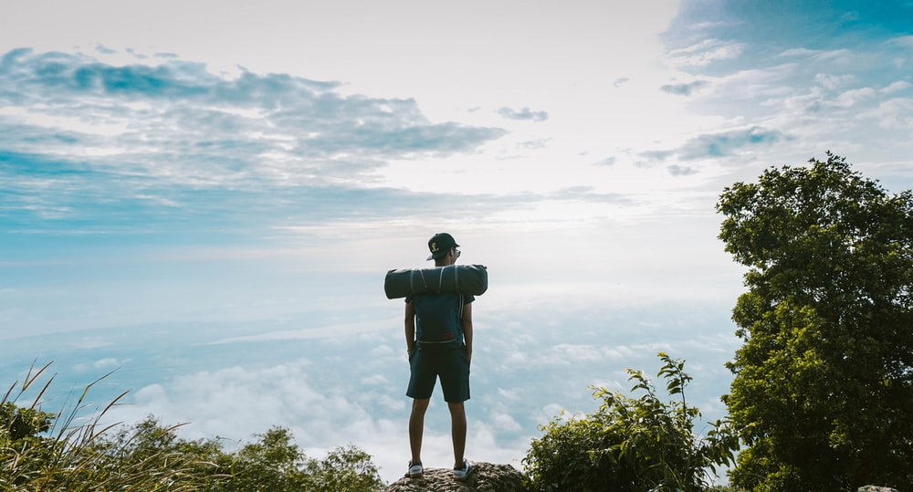 man in black shirt standing on cliff facing sea of clouds