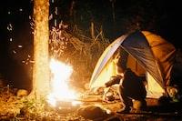 man cooking beside dome tent taken at nighttime