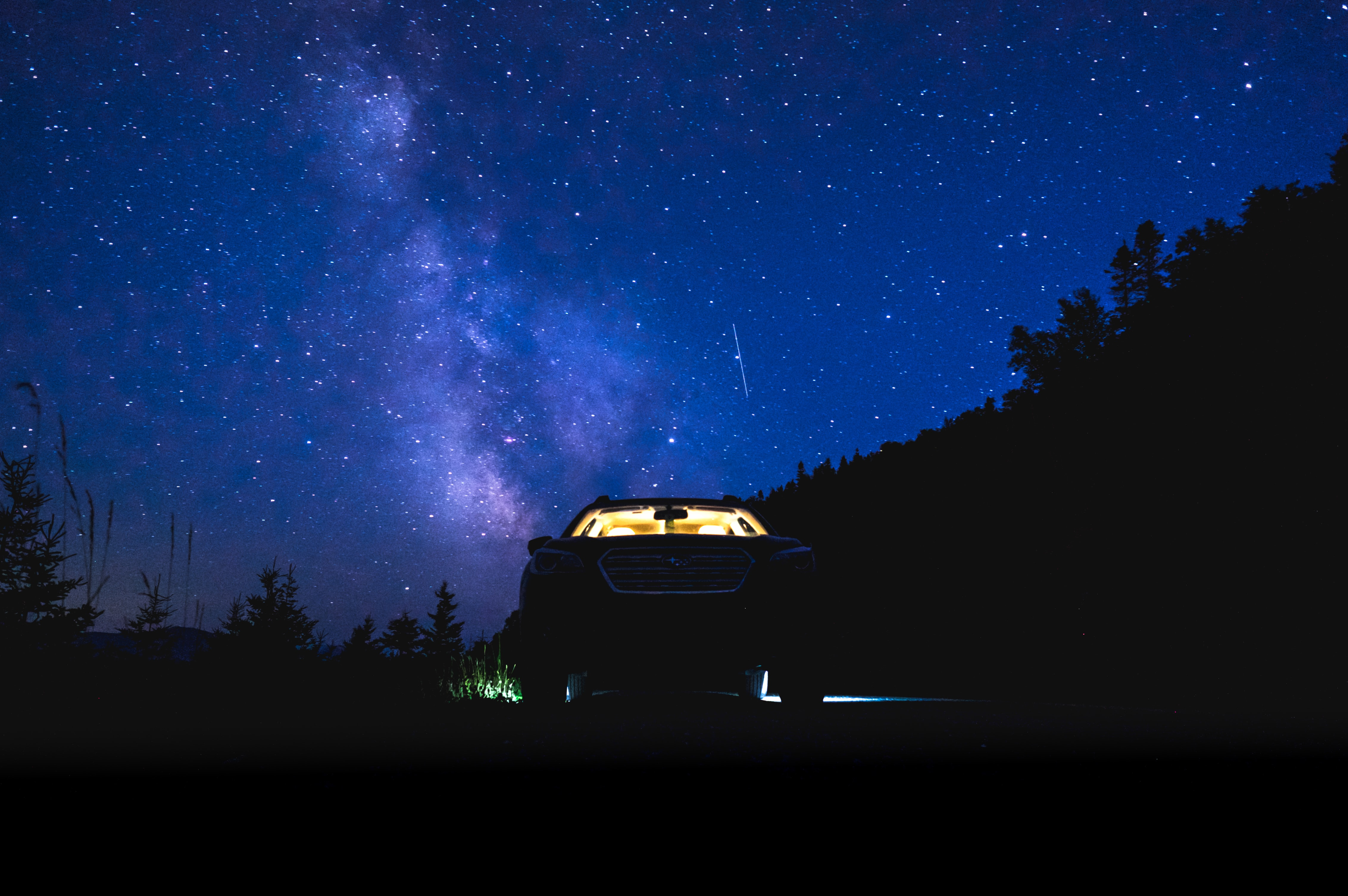 car parked in forest under starry sky