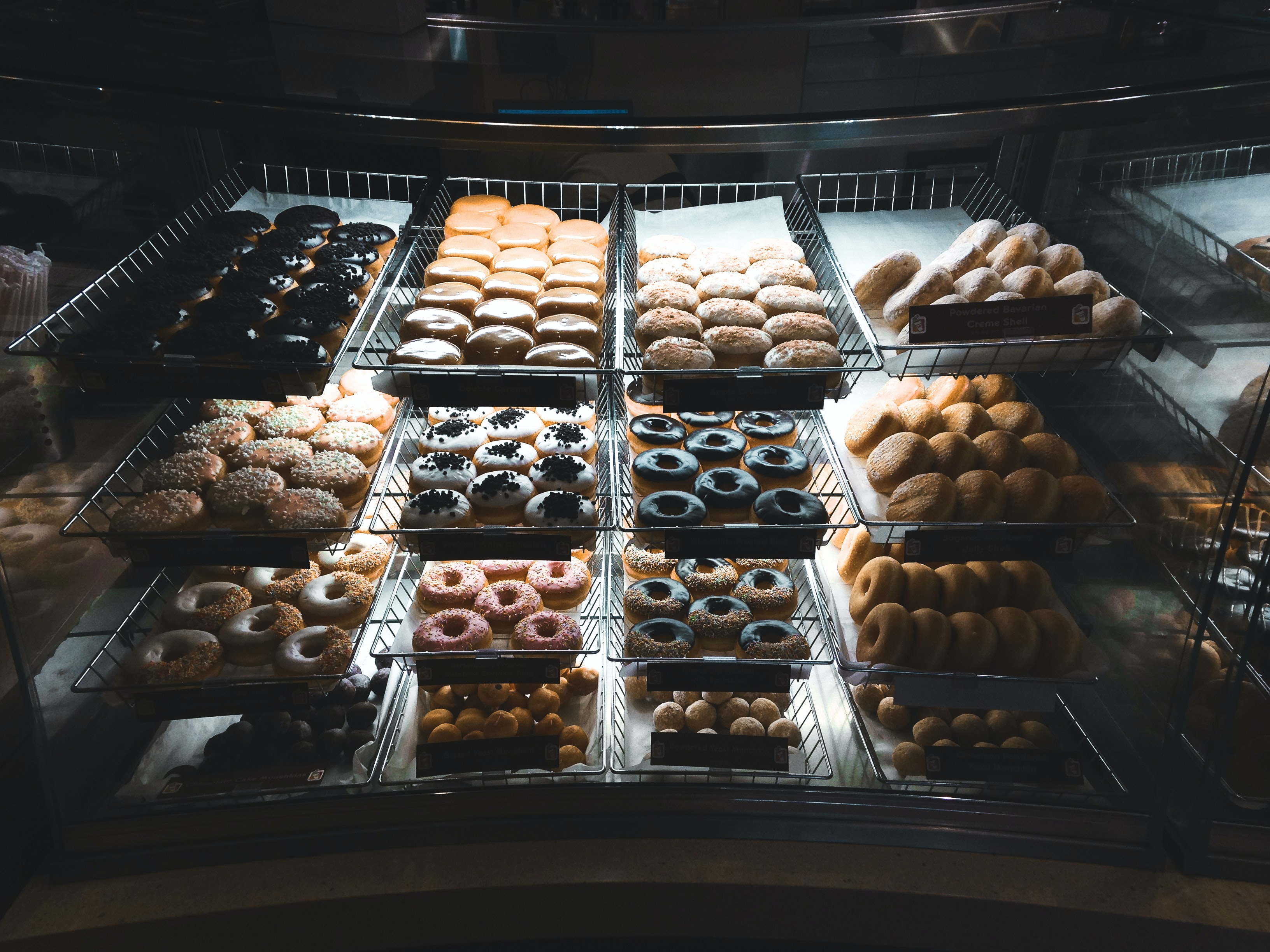 assorted-topping doughnuts on trays