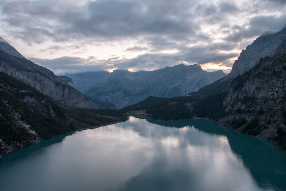 calm body of water between mountains under white clouds and blue sky