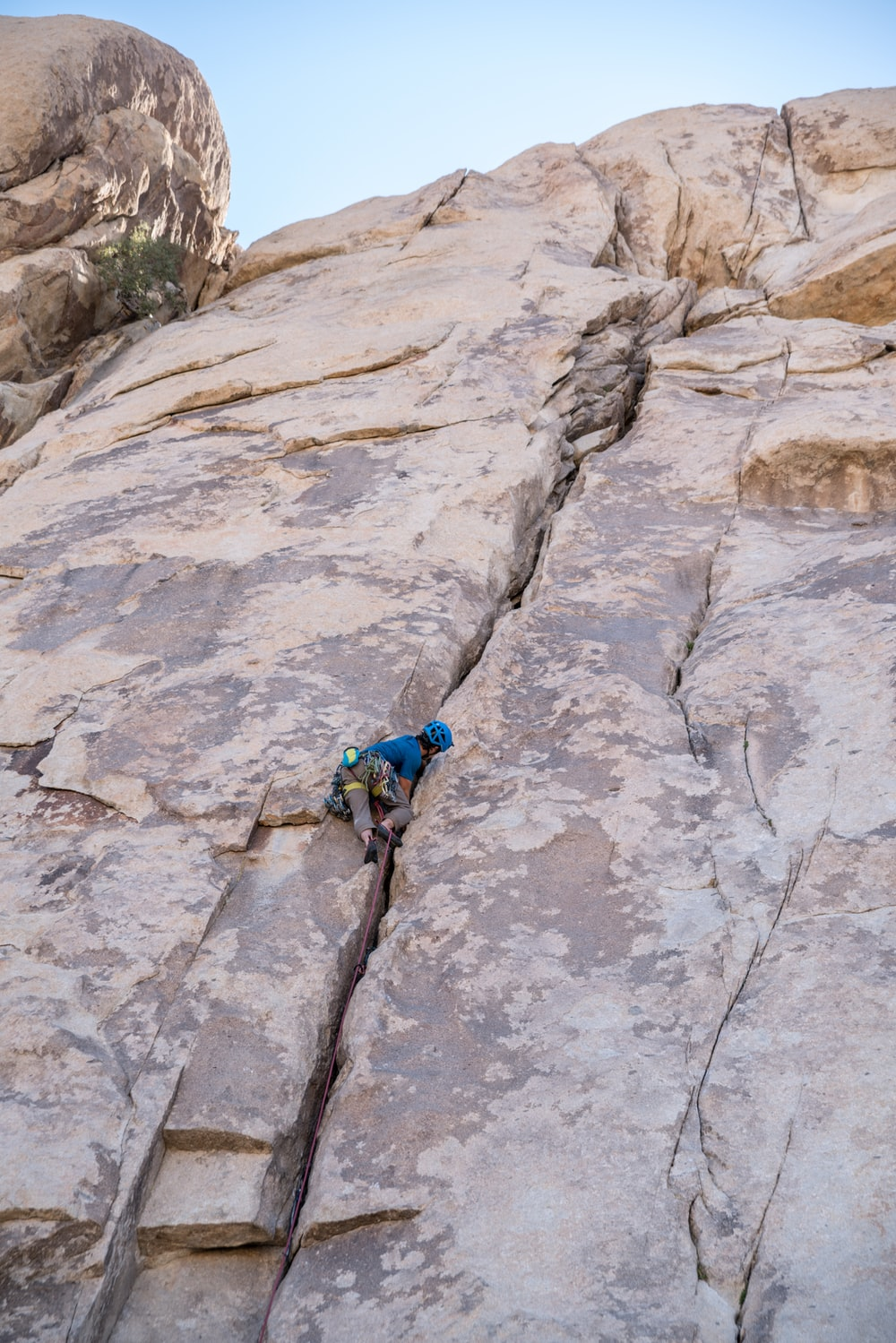 person in blue shirt climbing on brown mountain