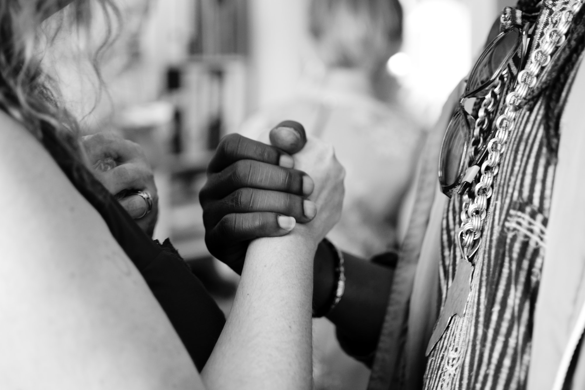 Two hands are clasped together, each half of a whole. Photo is in black-and-white.