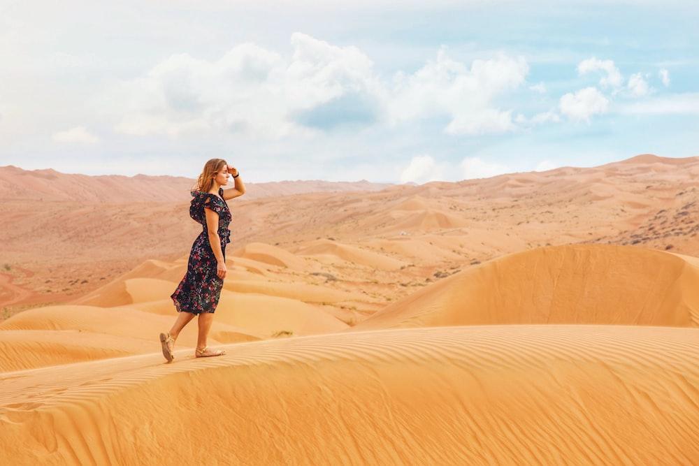 woman walking on sand dunes during daytime