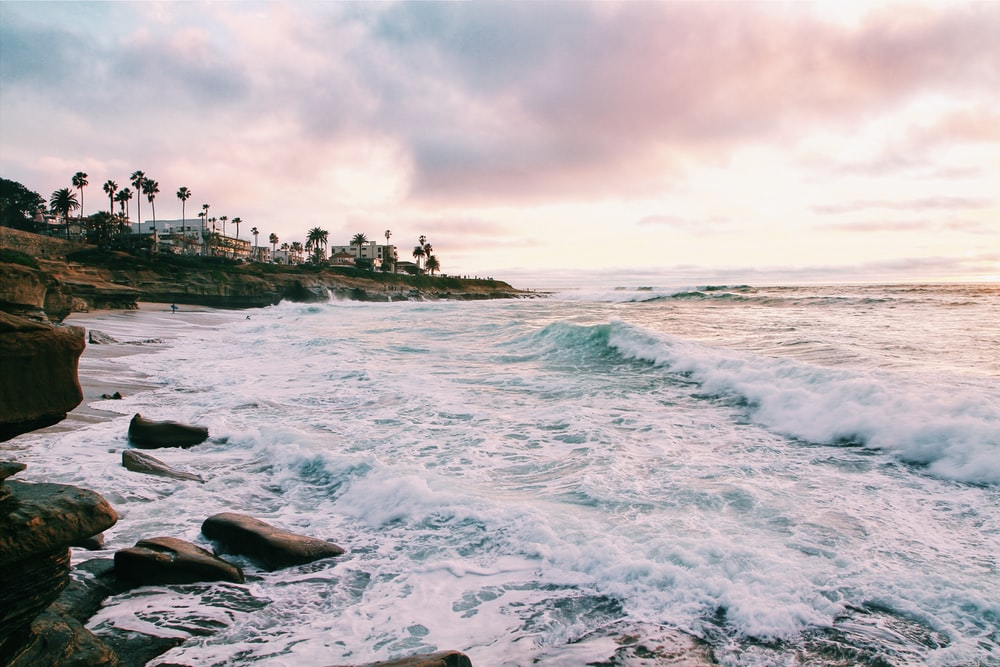sea waves crashing on shore during golden hour