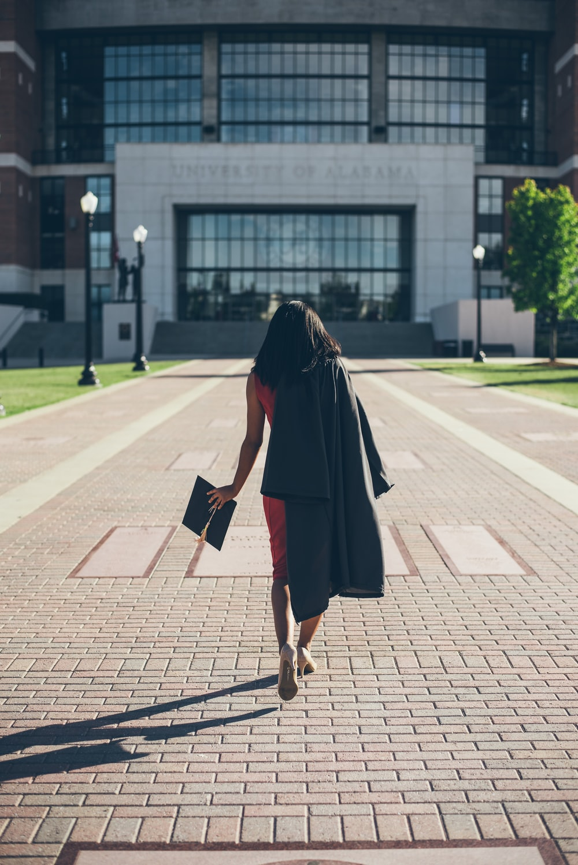 woman standing at facade of Alabama University building
