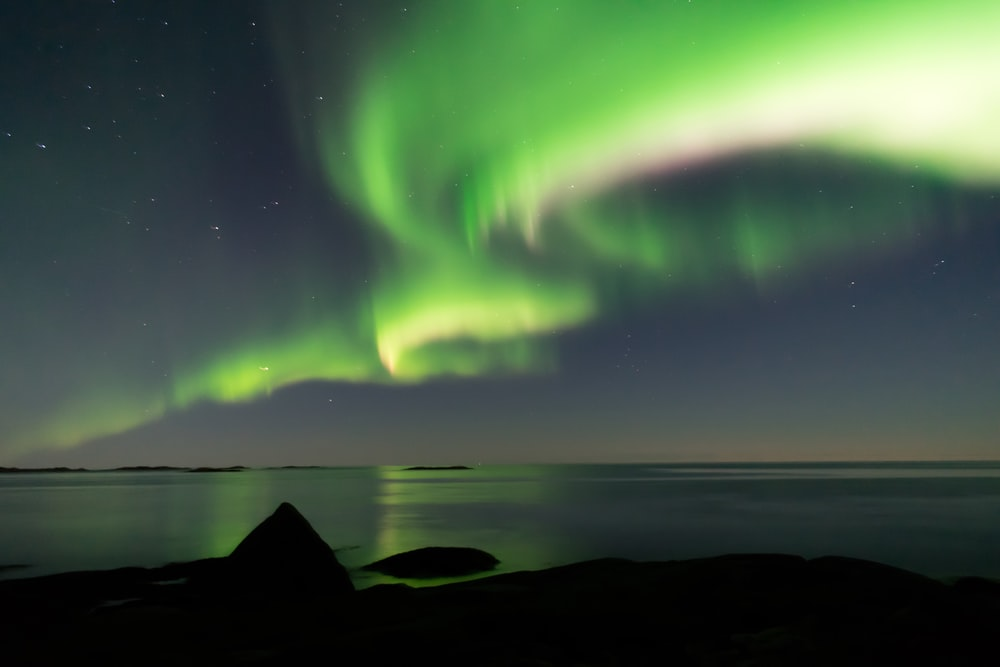 aurora borealis photography of body of water