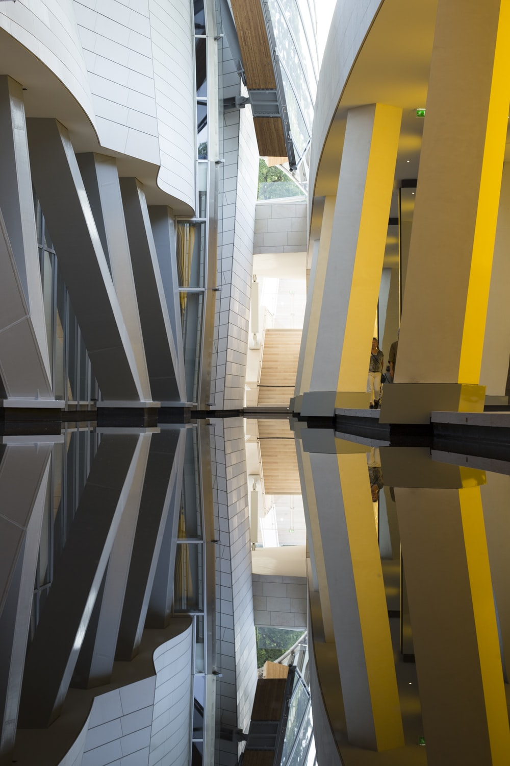 reflection of yellow and white building on water during daytime