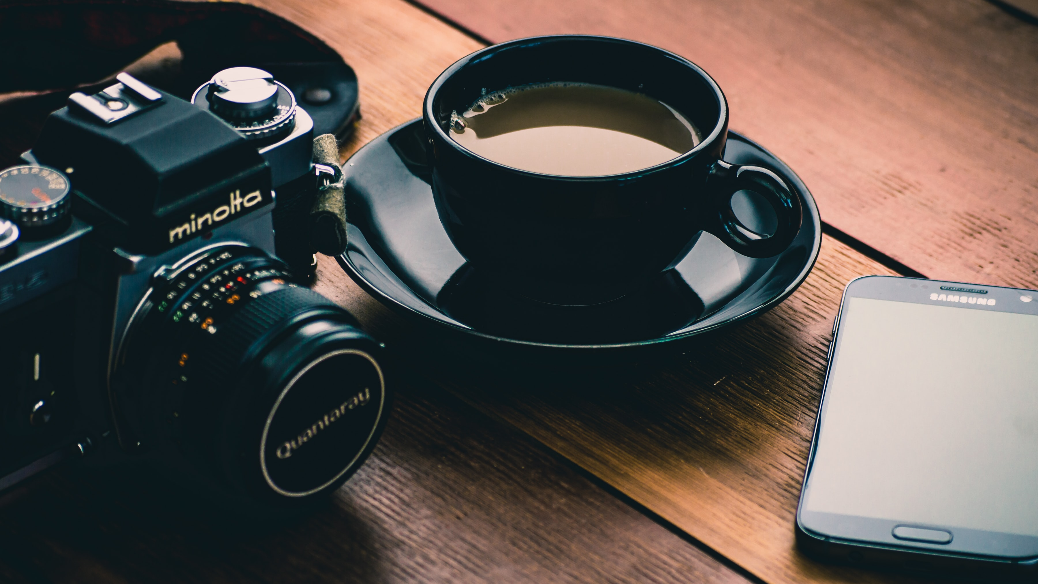 black Minolta camera beside coffee filled black ceramic cup