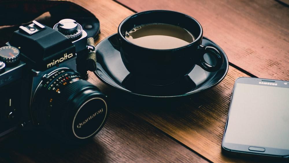 black Minolta camera beside coffee filled black ceramic cup