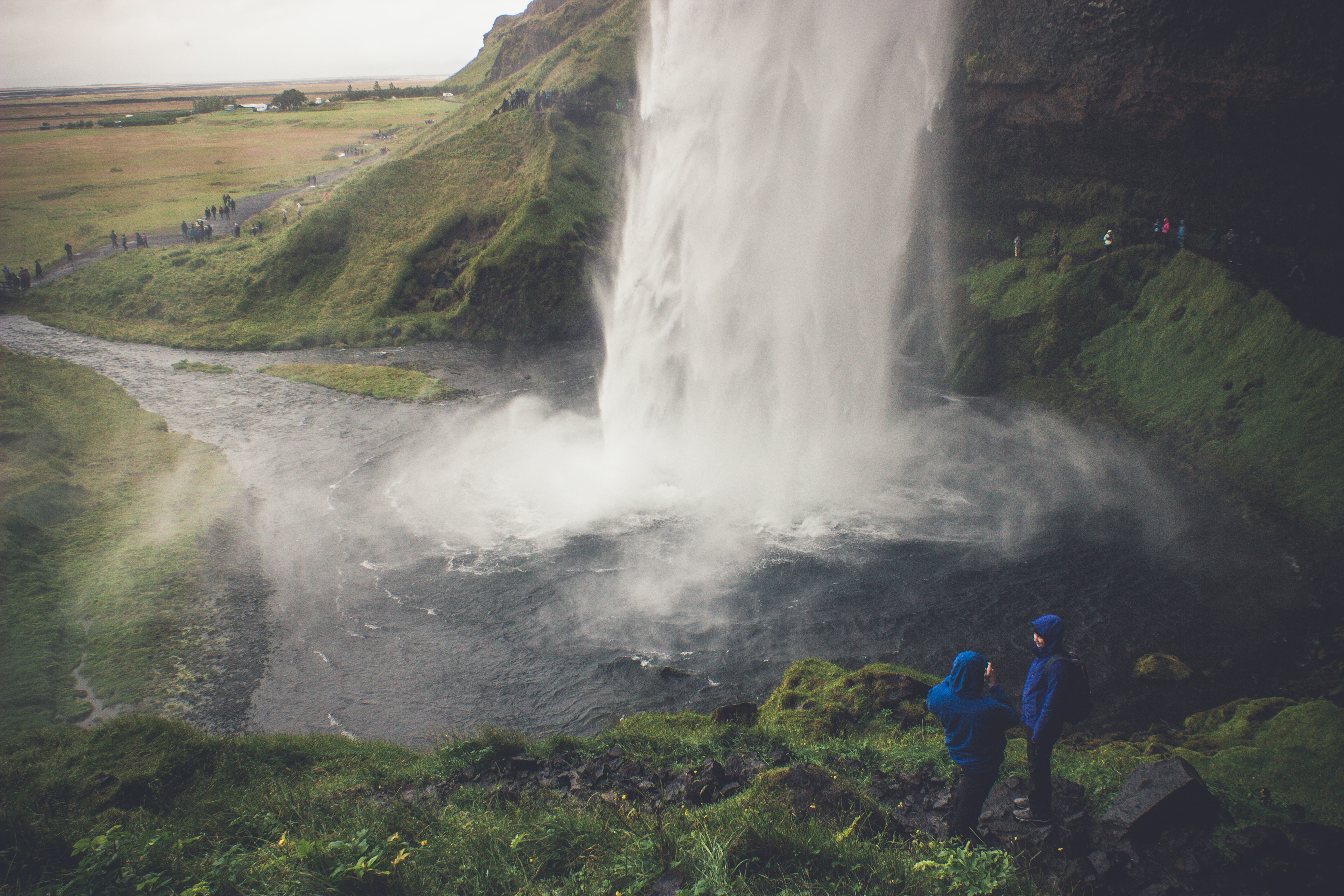 two person wearing blue hoodie standing on ground in front of waterfalls