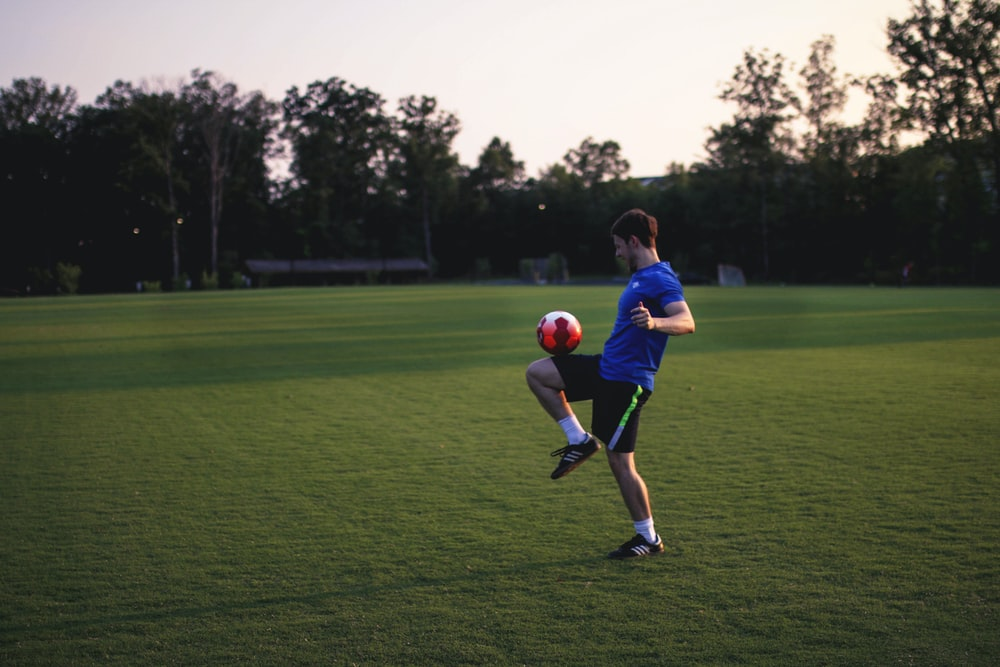 man juggling ball on grass field
