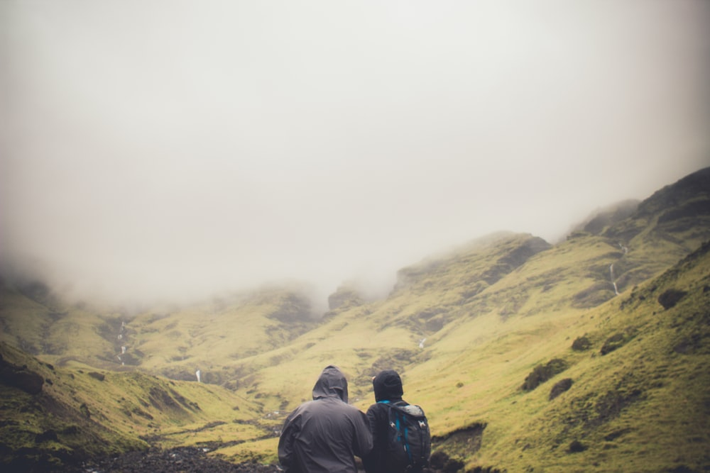 two people standing looking at mountians