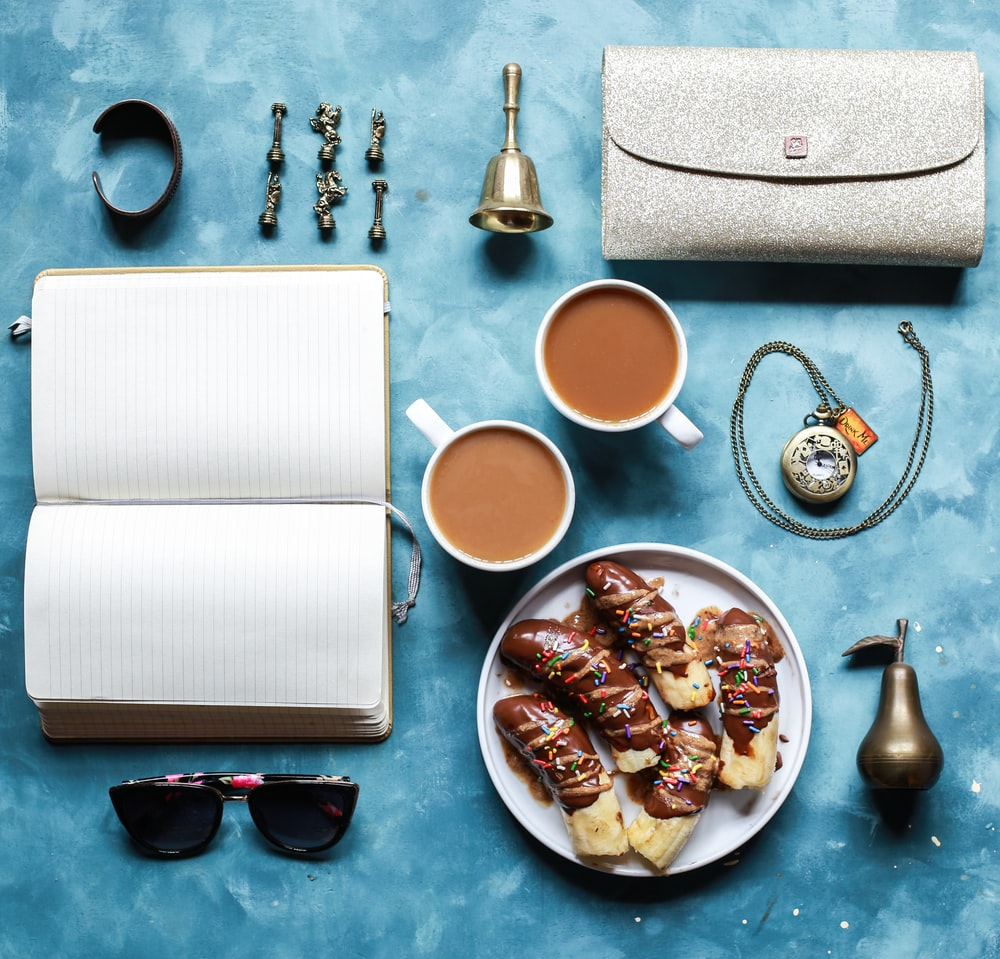 flat lay photography of opened book, coffee mugs, handbag, and sunglasses