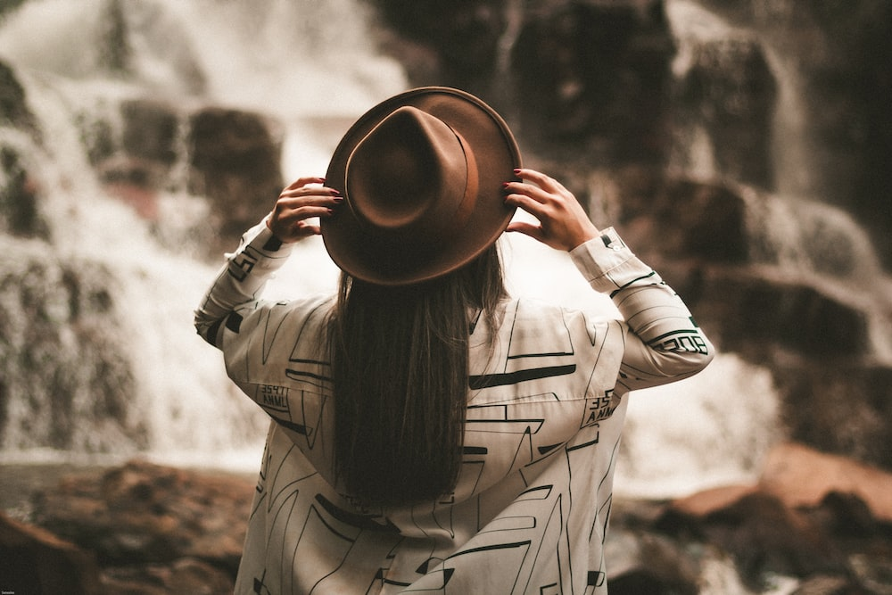 selective focus photography of woman holding brown fedora hat at daytime