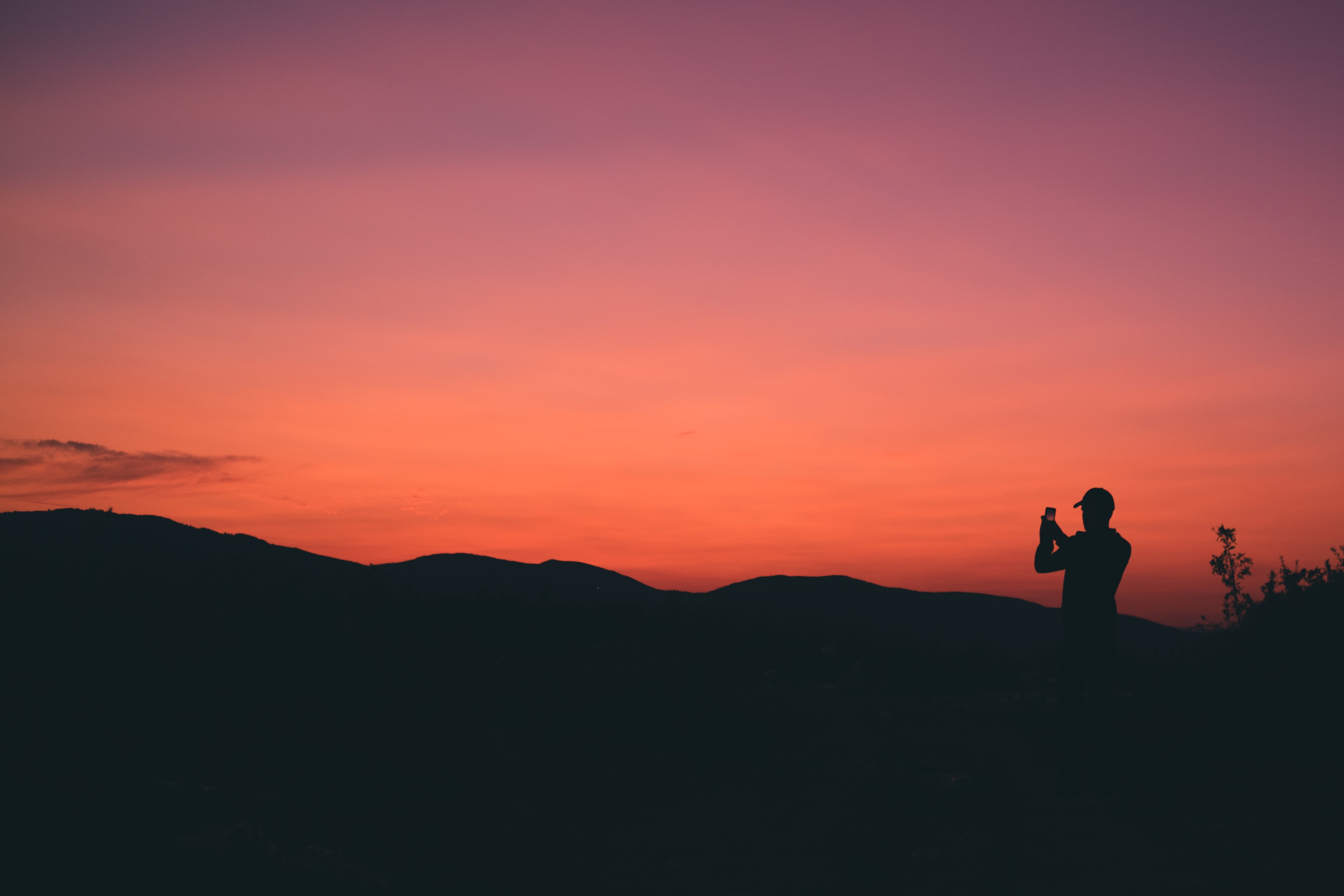 silhouette of person taking photo of mountain during sunset