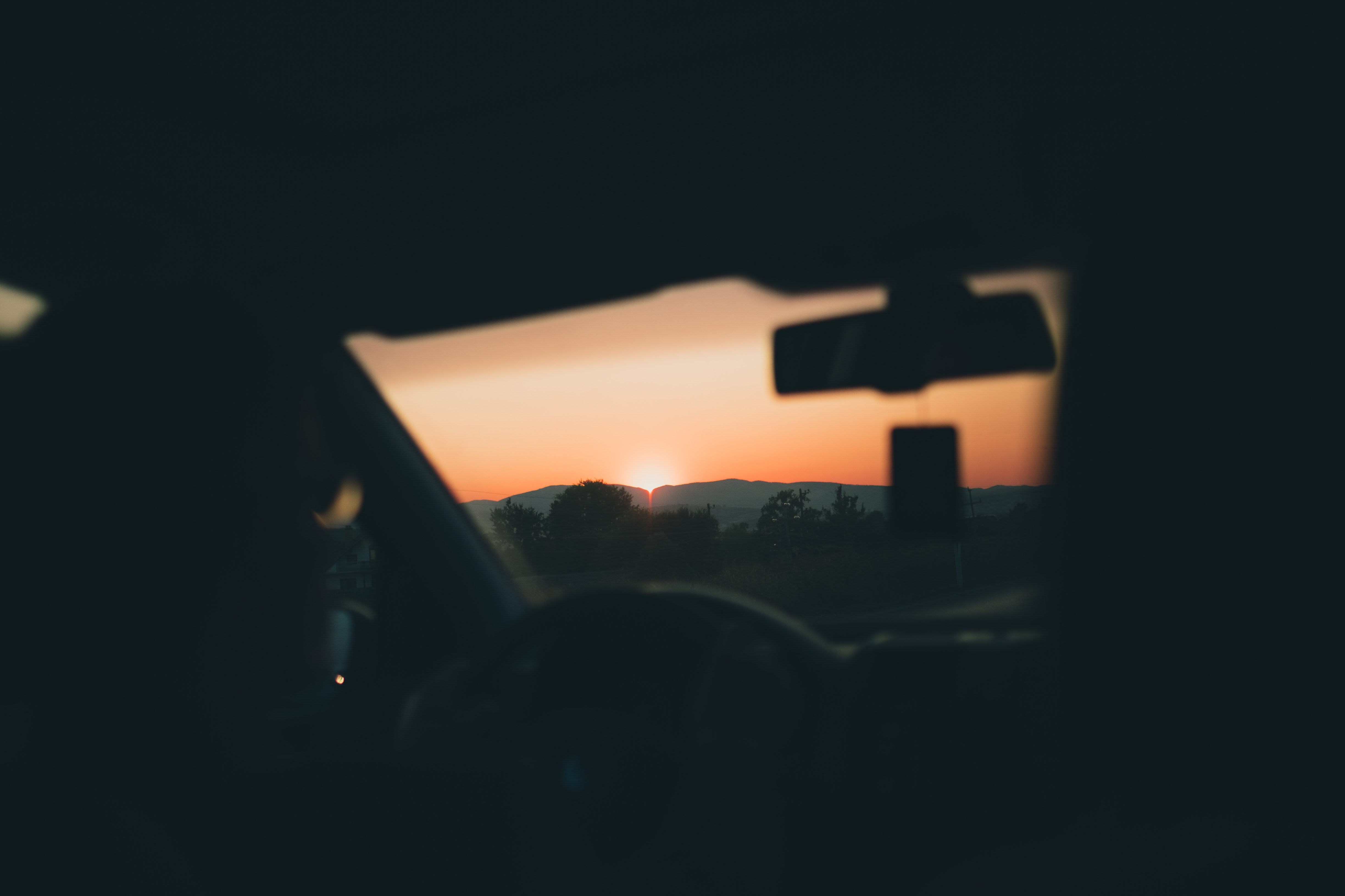 person in car seeing sunset