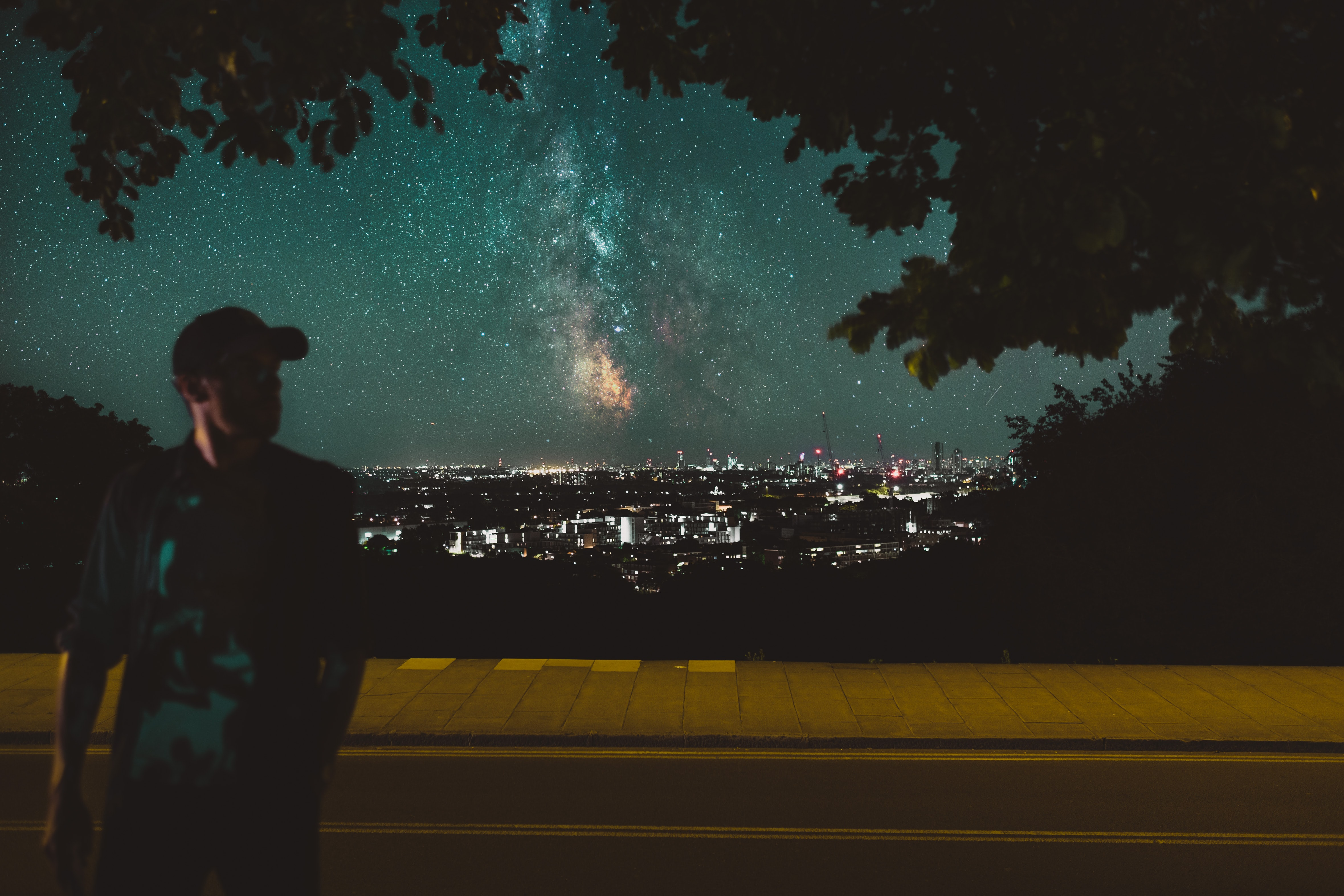 man walking on street with milky way galaxy view photo