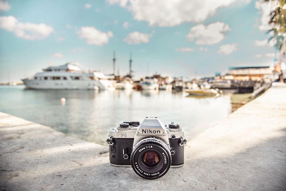 black and silver Nikon camera near boats during daytime