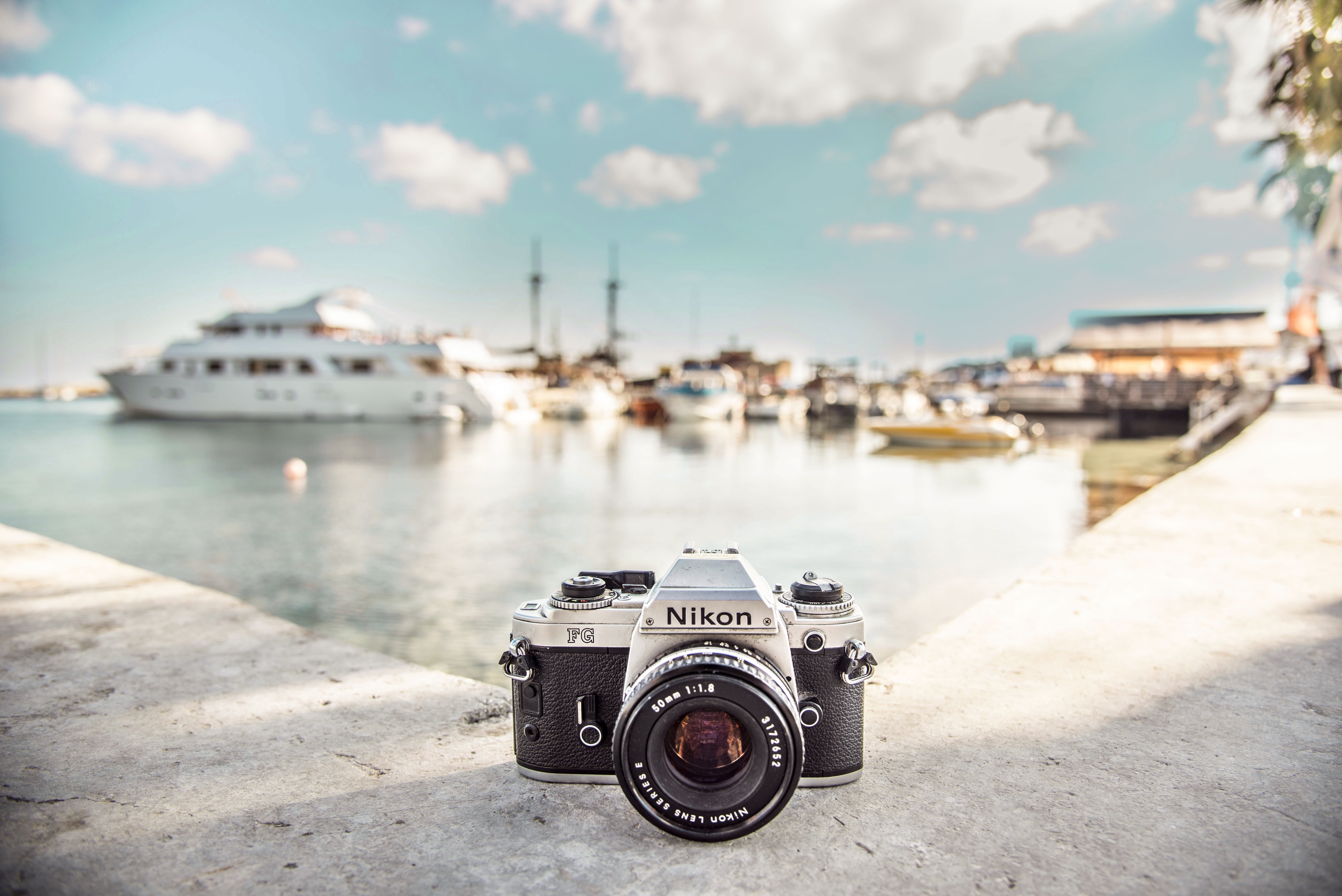 black and silver Nikon camera near boats during daytime
