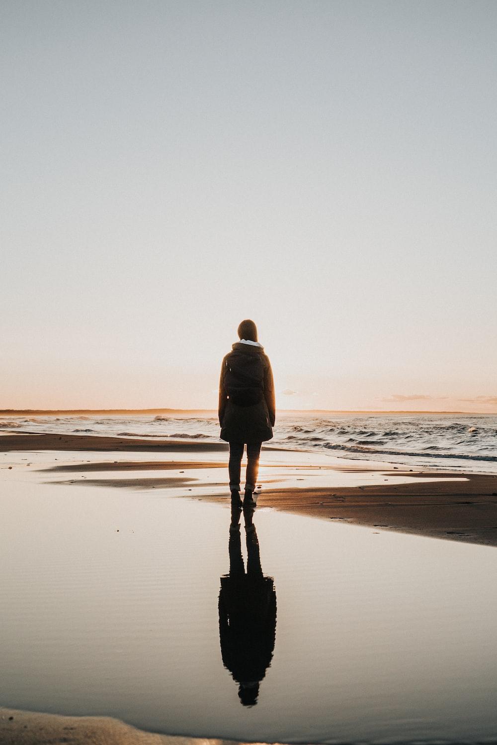 woman standing on sands near shoreline