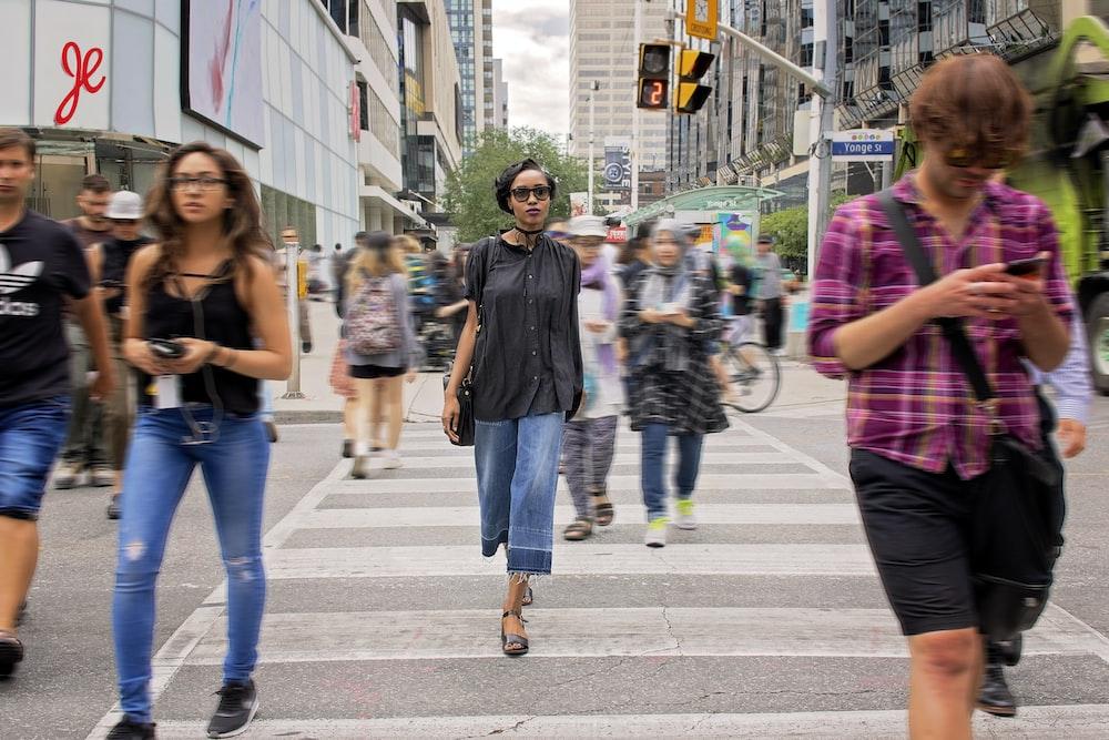 group of people passing through pedestrian lane during daytime
