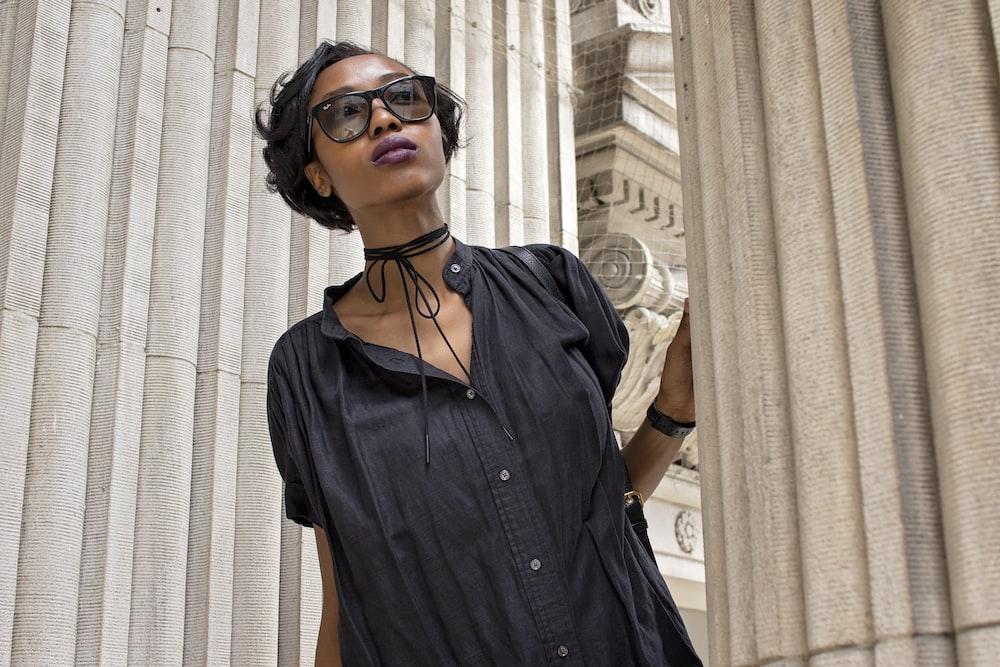 woman standing beside concrete pillar during daytime