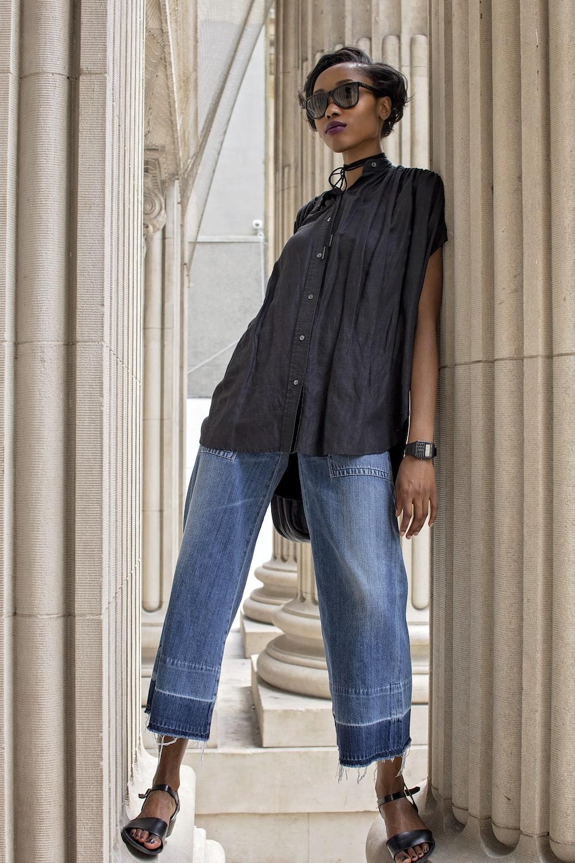 photo of woman leaning on pillar